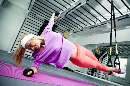 Young woman streching muscles making functional training