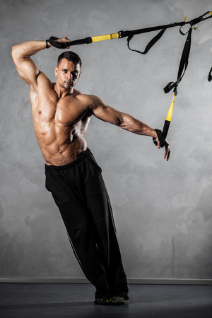 Young man stretching muscles making functional training