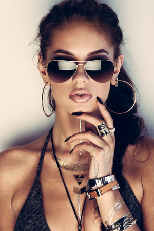 Photo pour Glamorous young woman with flash tattoos in sunglasses - image libre de droit