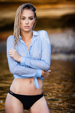 Young woman in wet shirt posing on a sand rocks near the sea