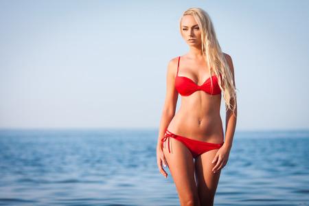 Sexy blond girl in red bikini posing on a beach
