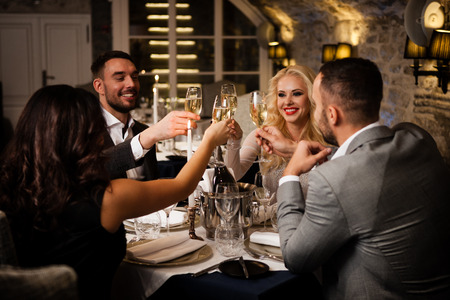 Photo for Four friends with champange glasses celebrating and toasting in restaurant - Royalty Free Image