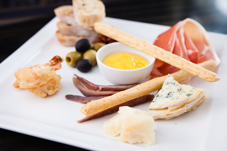 Tapas platter with variety of cheeses, ham and olivesの写真素材