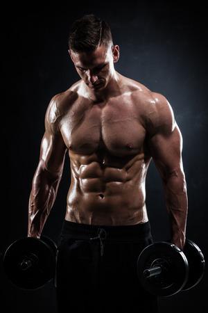 Foto de Athletic shirtless young male fitness model with dumbbells - Imagen libre de derechos