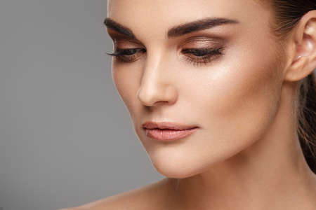 Photo pour Portrait of beautiful female model with clean natural skin on grey background - image libre de droit