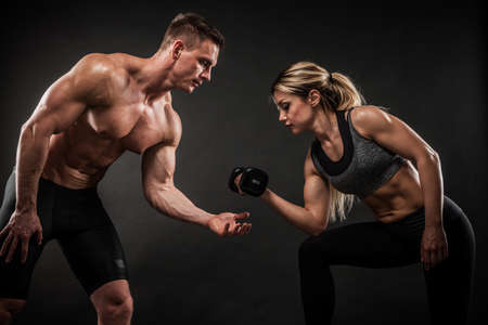 Photo pour Fitness in gym, sport and healthy lifestyle concept. Couple of athletic man and woman showing their trained bodies on black background. Two bodybuilder models standing and demonstrating tight muscles. - image libre de droit
