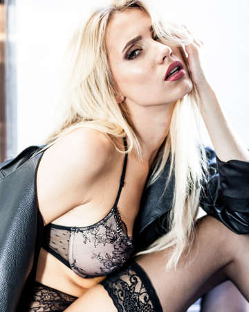 Foto de fashion and lingerie concept - beautiful blond lady portrait wearing sexy bra and panties in loft-style interior. Woman in underwear poses on a window in contrast light and shadows - Imagen libre de derechos