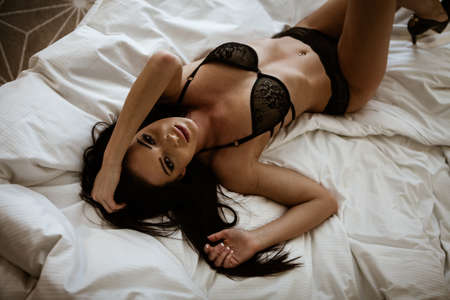 Photo pour Beauty of woman body and lingerie concept. Beautiful brunette female fashion model in sexy black underwear poses in luxury hotel room. Young girl lies on a bed in bedroom wearing bra and panties - image libre de droit