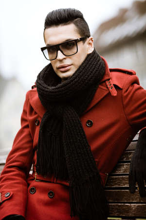 Photo pour LGBTQ community lifestyle concept. Young homosexual man sits on bench in city park. Handsome fashionable gay male model poses in cityscape outdoors. Wears red coat, gloves, sunglasses and black scarf - image libre de droit