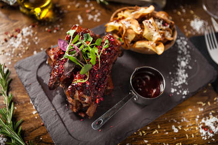Photo pour Pork ribs cooked at low temperature. Blackcurrant sauce, parsnip chips with Parmesan cheese. Delicious healthy meat food closeup served on a table for lunch in modern cuisine gourmet restaurant. - image libre de droit