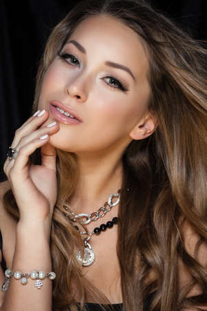 Foto de Perfect beauty and jewelry concept. Portrait of beautiful female model wearing ring, necklace and wristband on black background. Young blond woman shows glamorous finery. - Imagen libre de derechos