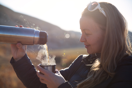 Photo for Campers drinking hot tea and coffeo from  bottle - Royalty Free Image
