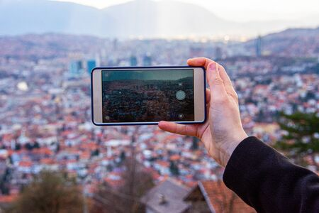 Photo for Person photographing cityscape of Sarajevo capital of BiH with mobile phone - Royalty Free Image