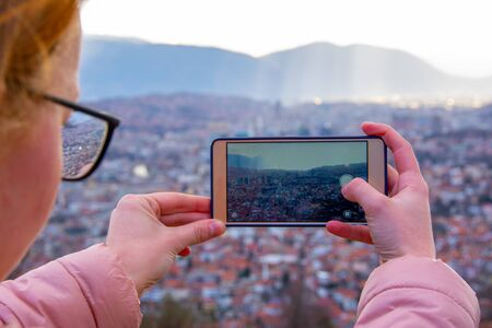 Photo for Girl with glasess and brown hair photographing cityscape of Sarajevo capital of BiH with mobile phone - Royalty Free Image