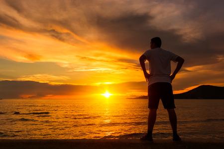 Foto de Young sports man doing stretching after run at the beach - Imagen libre de derechos