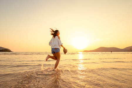 Photo pour A woman running in to the beach. Woman happy with vacation summer on the beach and sunset. - image libre de droit