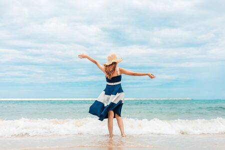 Photo pour Happy Woman in summer vacation wearing hat and dress enjoying the view at the island beach. - image libre de droit
