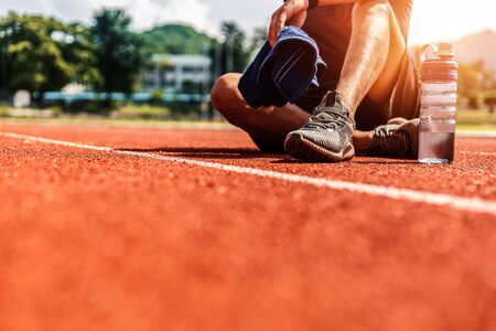 Foto per Sport man sitting and holding  towel on track race near water bottle at sport stadium in the morning. - Immagine Royalty Free
