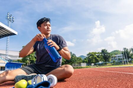 Foto per Sport man sitting and holding water bottle on track race at sport stadium in the morning. enjoy and lifestyle concept. - Immagine Royalty Free