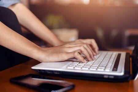 Photo pour woman's hands typing on a laptop on a wooden desk. - image libre de droit