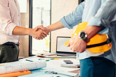 Photo pour Architect and businessman handshake after finish an agreement in the office at  site construction. - image libre de droit