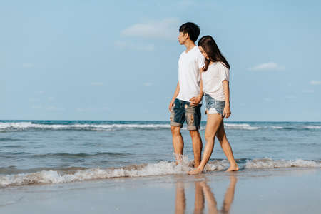 Photo pour Romantic couple holding hands and walking on beach. Man and woman in love. - image libre de droit