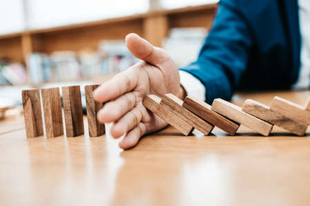 Photo pour Businessman protect wooden block fall to planning and strategy in risk to business Alternative and prevent. - image libre de droit