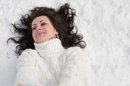 Happy girl lying down on the snow in winter.