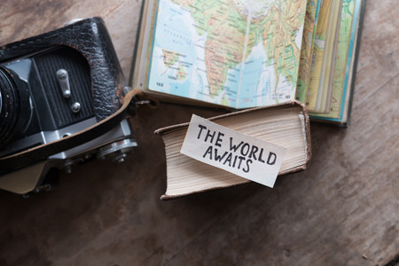 "text ""The World Awaits"" and book, travel, tour,tourism concept"