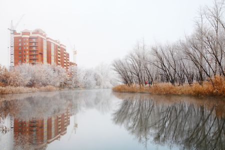 Autumn landscape with river and frosty trees