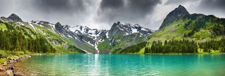 Mountain landscape with turquoise lake and cloudy sky