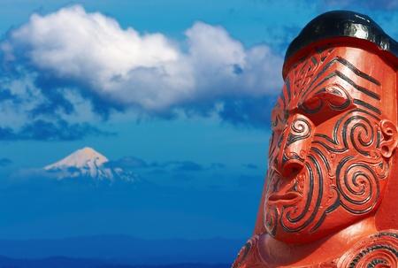 Foto de Traditional maori carving and Taranaki Mount, New Zealand  - Imagen libre de derechos
