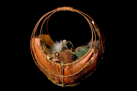 Photo of wooden basket with toy hedgehog and fir branch and wooden kitchenware and wine bottle in it isolated on black background