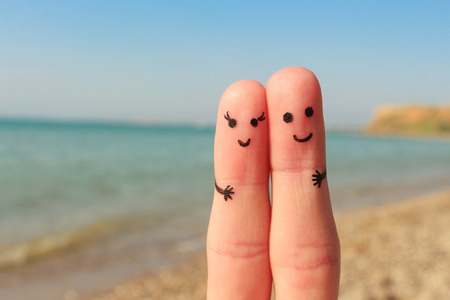 Finger art of a Happy couple. Man and woman have a rest on the beach sea. Man and woman hug on the background sea.