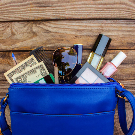 Things from open lady handbag. women's purse on wood background. Cosmetics, money and women's accessories fell out of the blue handbag.