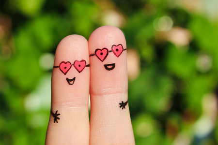 Finger art of a Happy couple. A man and a woman hug in pink glasses in shape of hearts. The concept of love at first sight.