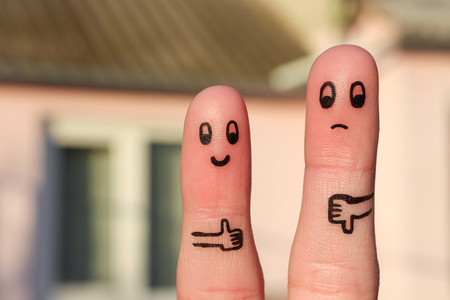 Finger art of couple. Woman showing thumbs up and man showing thumbs down. Concept of disagreement in family.