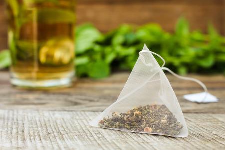 Photo pour Tea bag on background of mint and and cup of tea - image libre de droit