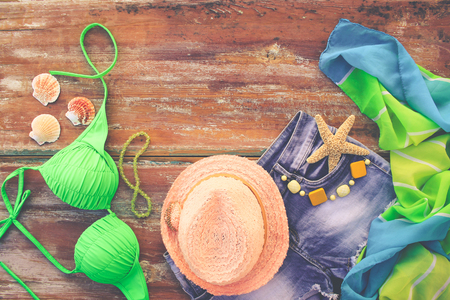 Summer women's clothing and accessories: hat, bathing suit, denim shorts, pareo, shells. Toned image. Top view.