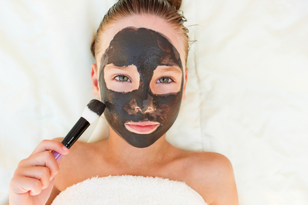 Beautiful girl with facial black clay mask. Top view.