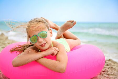 Photo pour Happy girl lying on pink inflatable circle. - image libre de droit