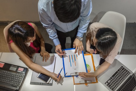 Asian business people discuss about the sales report