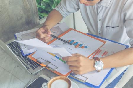 Photo pour Office man holding pen and checking financial report - image libre de droit
