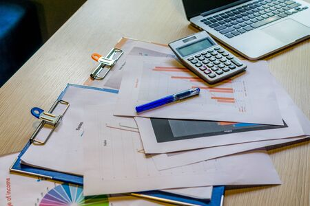 Photo pour Busy cluttered working desk with laptop calculator and documents - image libre de droit
