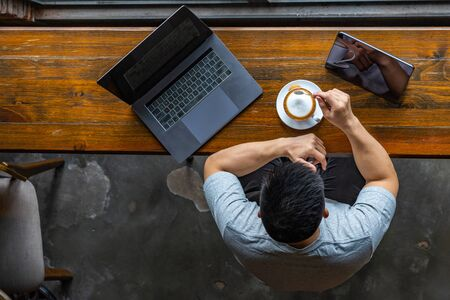 Photo for Asian freelancer working with laptop and enjoying hot cappuccino - Royalty Free Image