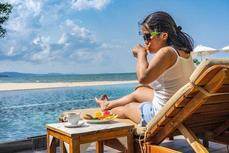 Photo pour Asian woman drinking orange juice at the luxury resort - image libre de droit