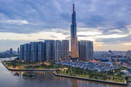 Foto für Tall buildings on along riverbank under cloudy sky in evening - Lizenzfreies Bild