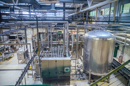 Modern brewery production line. Large vat for beer  fermentation and maturation, pipelines and filtration system.