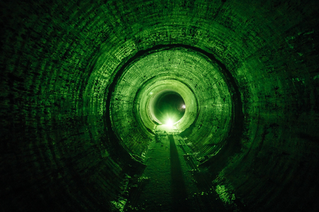 Flooded round underground drainage sewer tunnel with dirty sewage water green illuminated.