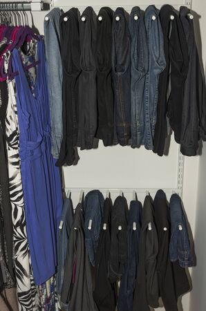 Foto per Close up view of interior of built-in wardrobe. Blue and black jeans on white hangers. Cloth organizer. - Immagine Royalty Free